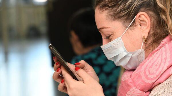 Devushka v zaщitnoy maske so smartfonom v rukax - arxivnoye foto - Sputnik Oʻzbekiston