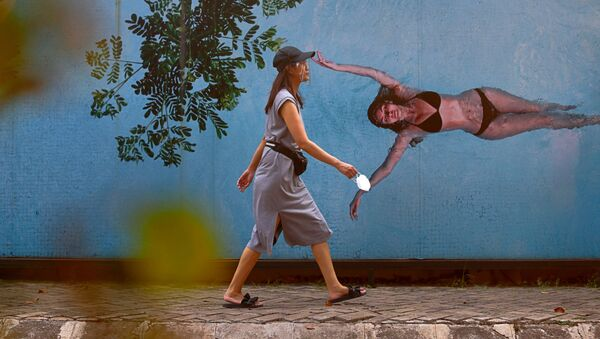 Графити фонида ҳимоя ниқобини таққан аёл, Жакарта, Индонезия. - Sputnik Ўзбекистон