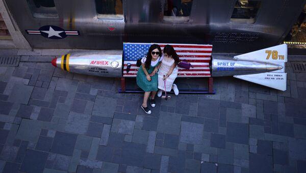 Девушки фотографируются на скамейке-ракете внутри пекинского магазина - Sputnik Узбекистан