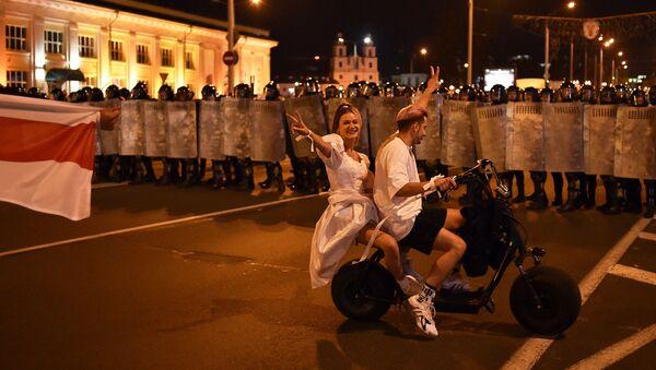 Пара на скутере перед ОМОНом во время акции протеста после закрытия избирательных участков на президентских выборах в Беларуси - Sputnik Узбекистан
