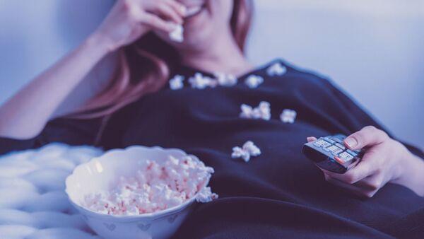 Devushka v posteli yest popkorn i derjit pult. Arxivnoye foto - Sputnik Oʻzbekiston