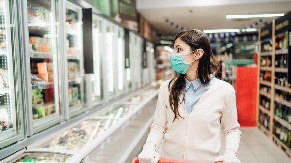 Pokupatelnitsa v maske i perchatkax v produktovom magazine - Sputnik Oʻzbekiston