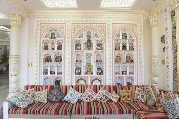 Подушки из сюзане, посуда из керамики и миниятюры на стене зоны отдыха - Sputnik Узбекистан