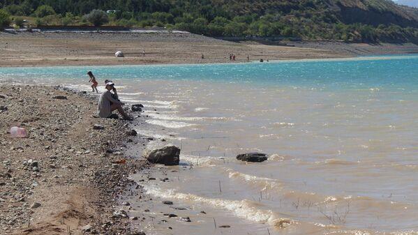 Уровень воды в водохранилище заметно упал, оголив глинистое дно. Многие предпочитают просто позагорать на берегу. - Sputnik Узбекистан