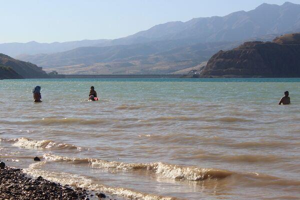 Вода из-за суглинистого дна очень мутная, но желание окунуться в жаркую погоду для многих оказывается сильнее - Sputnik Узбекистан