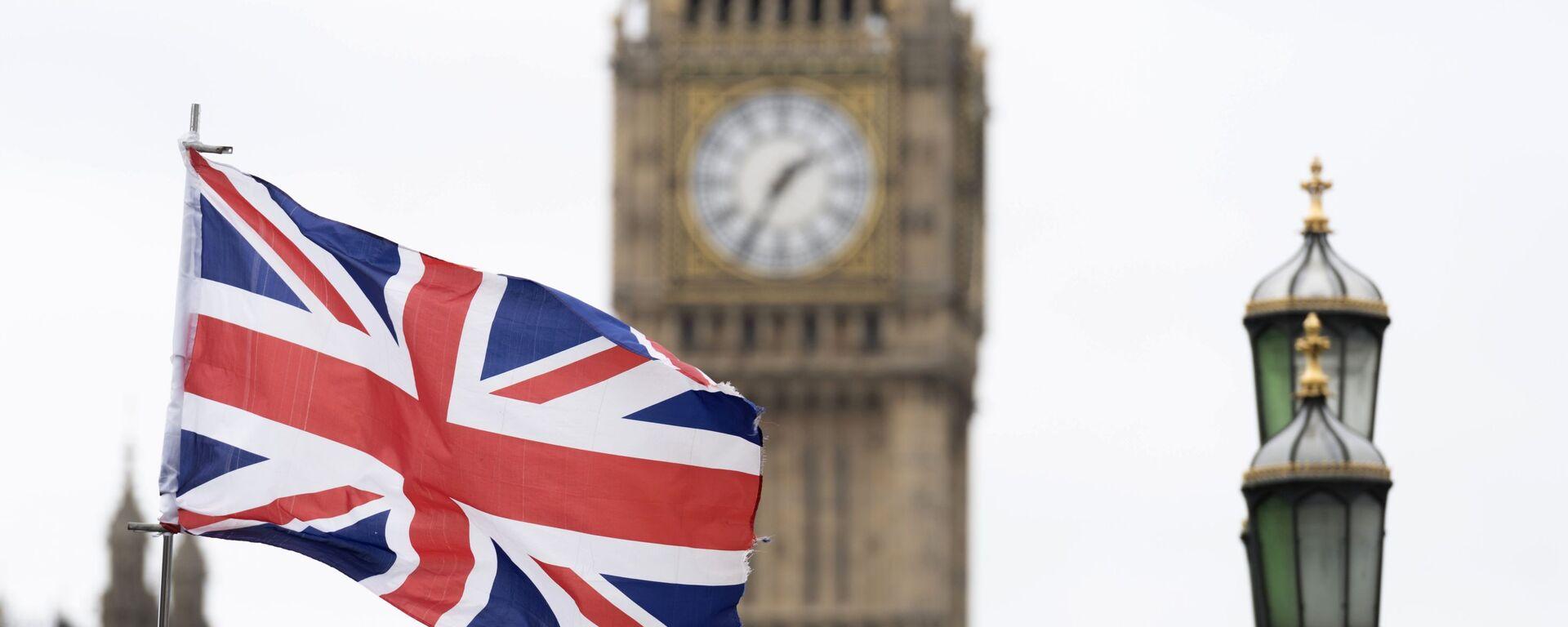 Флаг Великобритании на фоне Вестминстерского дворца в Лондоне - Sputnik Узбекистан, 1920, 30.03.2021