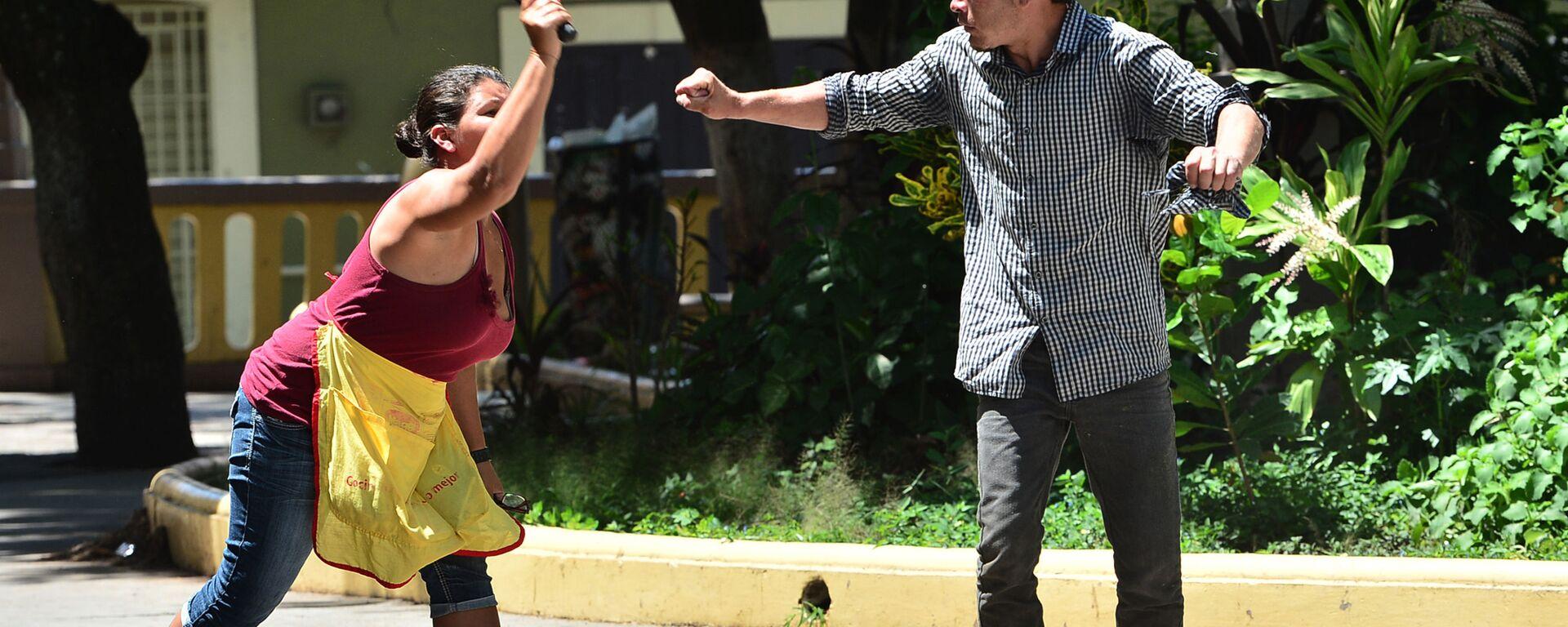 Женщина нападает на мужчину во время антиправительственной акции протеста против мер борьбы с коронавирусом в Тегусигальпе, Гондурас - Sputnik Узбекистан, 1920, 05.06.2021