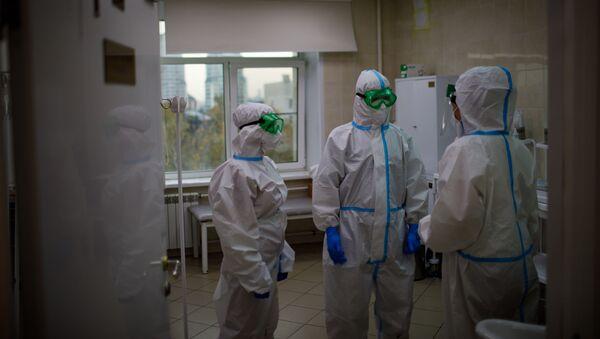 Медицинские работники оказывают помощь пациенту с COVID-19 - Sputnik Узбекистан