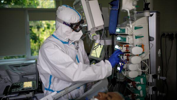 Медицинский работник оказывает помощь пациенту с COVID-19  - Sputnik Узбекистан