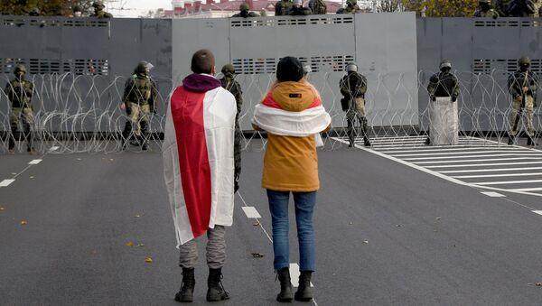 Участники несанкционированной властями акции протеста Партизанский марш у оцепления правоохранительных сил в Минске - Sputnik Узбекистан