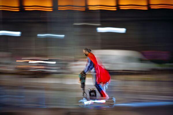Мужчина в костюме супермена едет на скутере по улице Бухареста, Румыния - Sputnik Ўзбекистон