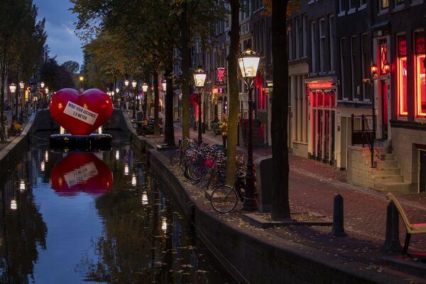Красное сердце с напоминанием соблюдать социальную дистанцию в почти пустом квартале красных фонарей в Амстердаме, Нидерланды - Sputnik Ўзбекистон