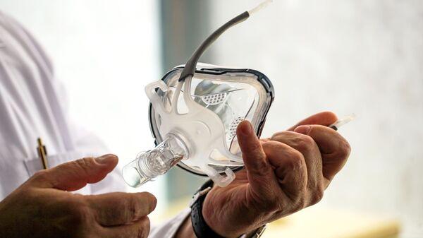 Врач держит в руках маску для искусственной вентиляции легки - Sputnik Узбекистан