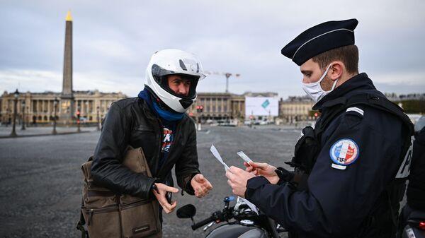 Французский полицейский проверяет документы мотоциклиста на площади Согласия в Париже, Франция - Sputnik Узбекистан