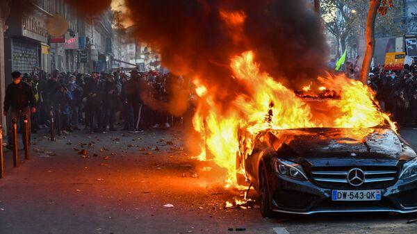 Горящий автомобиль во время акции недовольства действиями правоохранительных органов в отношении мигрантов и против внесения поправки к закону О национальной безопасности в Париже - Sputnik Узбекистан