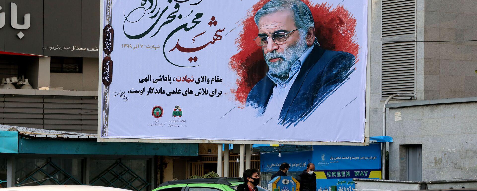 Автомобили проезжают мимо плаката с изображением ученого-ядерщика Мохсена Фахризаде в Тегеране, Иран - Sputnik Узбекистан, 1920, 02.12.2020
