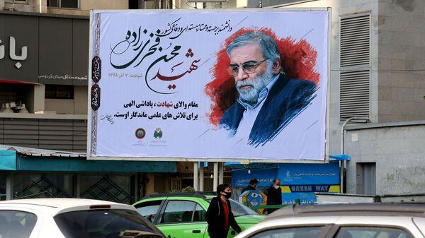 Автомобили проезжают мимо плаката с изображением ученого-ядерщика Мохсена Фахризаде в Тегеране, Иран - Sputnik Узбекистан