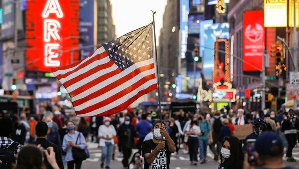 Мужчина с флагом США на Таймс-сквер в Нью-Йорке - Sputnik Узбекистан