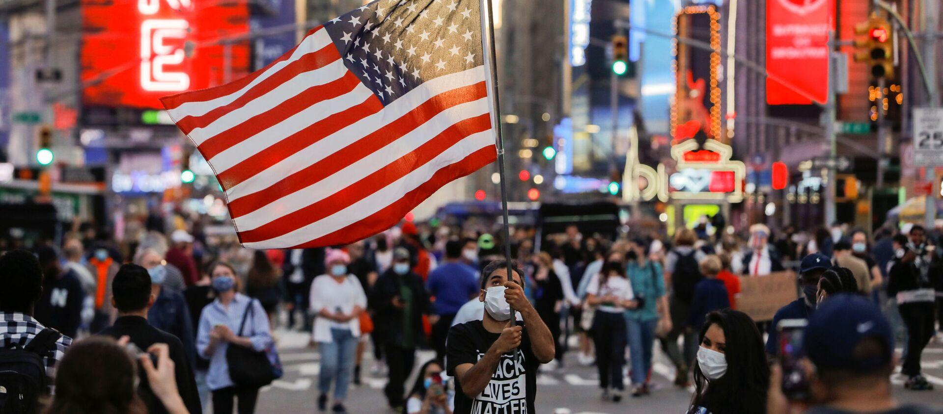 Мужчина с флагом США на Таймс-сквер в Нью-Йорке - Sputnik Узбекистан, 1920, 02.12.2020