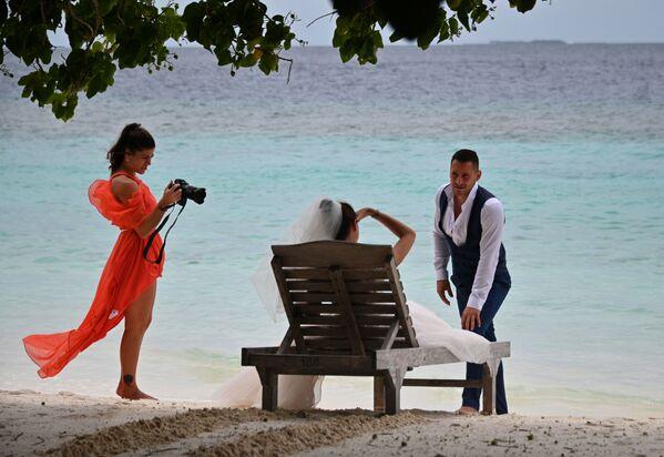 Molodojenы fotografiruyutsya na plyaje odnogo iz Maldivskix ostrovov, poluchivshix zvaniye World's Leading Destination 2020 - Sputnik Oʻzbekiston