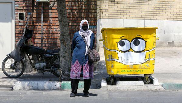Женщина в защитной маске у разрисованного мусорного бака в Тегеране  - Sputnik Ўзбекистон