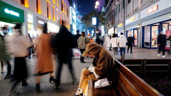 Девушка с мобильником в главном торговом районе Уханя через год после начала вспышки коронавируса, Китай - Sputnik Ўзбекистон