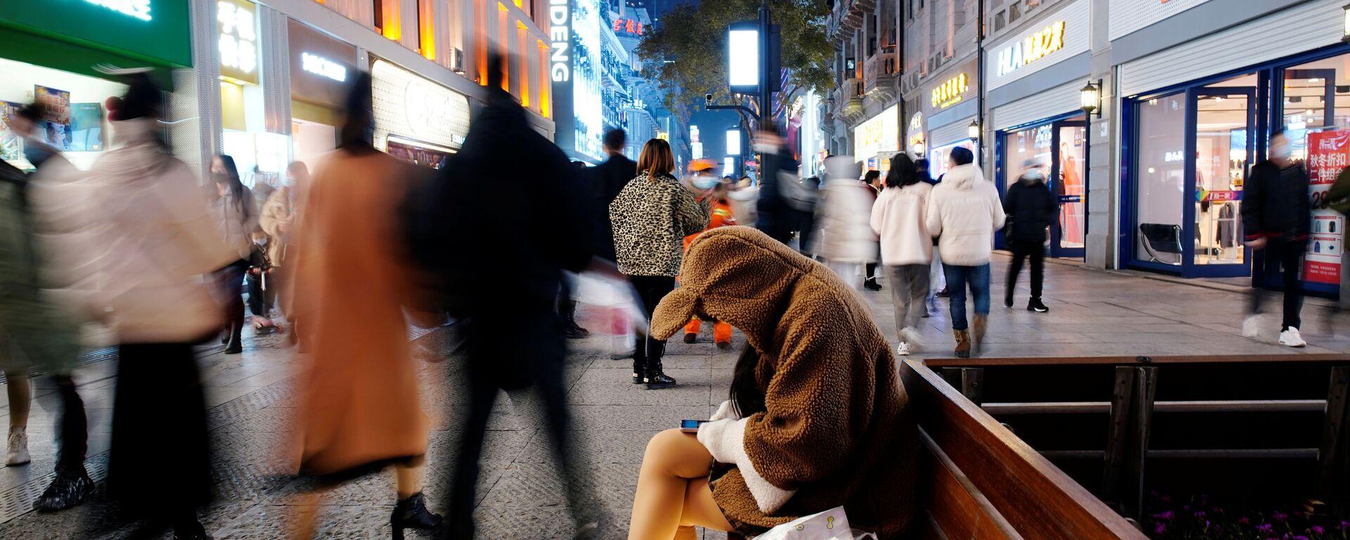 Девушка с мобильником в главном торговом районе Уханя через год после начала вспышки коронавируса, Китай - Sputnik Ўзбекистон, 1920, 27.09.2021