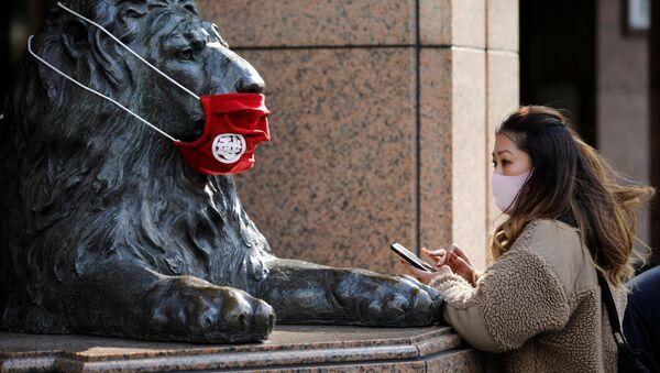 Jenщina v zaщitnoy maske pered statuyey v Tokio  - Sputnik Oʻzbekiston