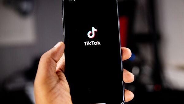 Izobrajeniye logotipa sotsialnoy seti TikTok na ekrane telefona - Sputnik Oʻzbekiston