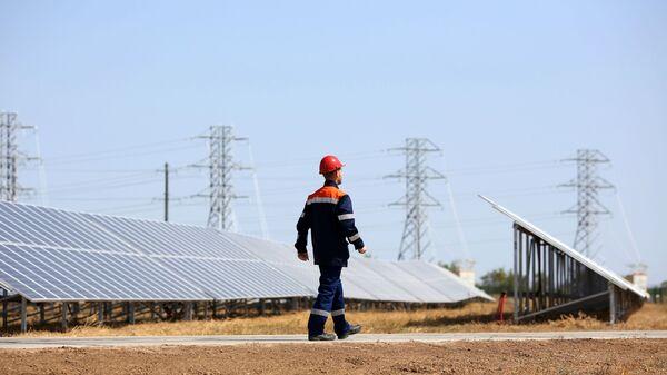Сотрудник осматривает состояние фотоэлектрических элементов на солнечных панелях солнечной электростанции - Sputnik Узбекистан