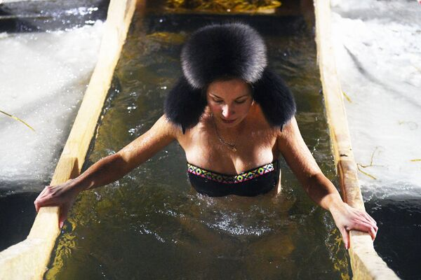 Девушка во время крещенского купания в проруби на реке Обь в черте Новосибирска - Sputnik Узбекистан