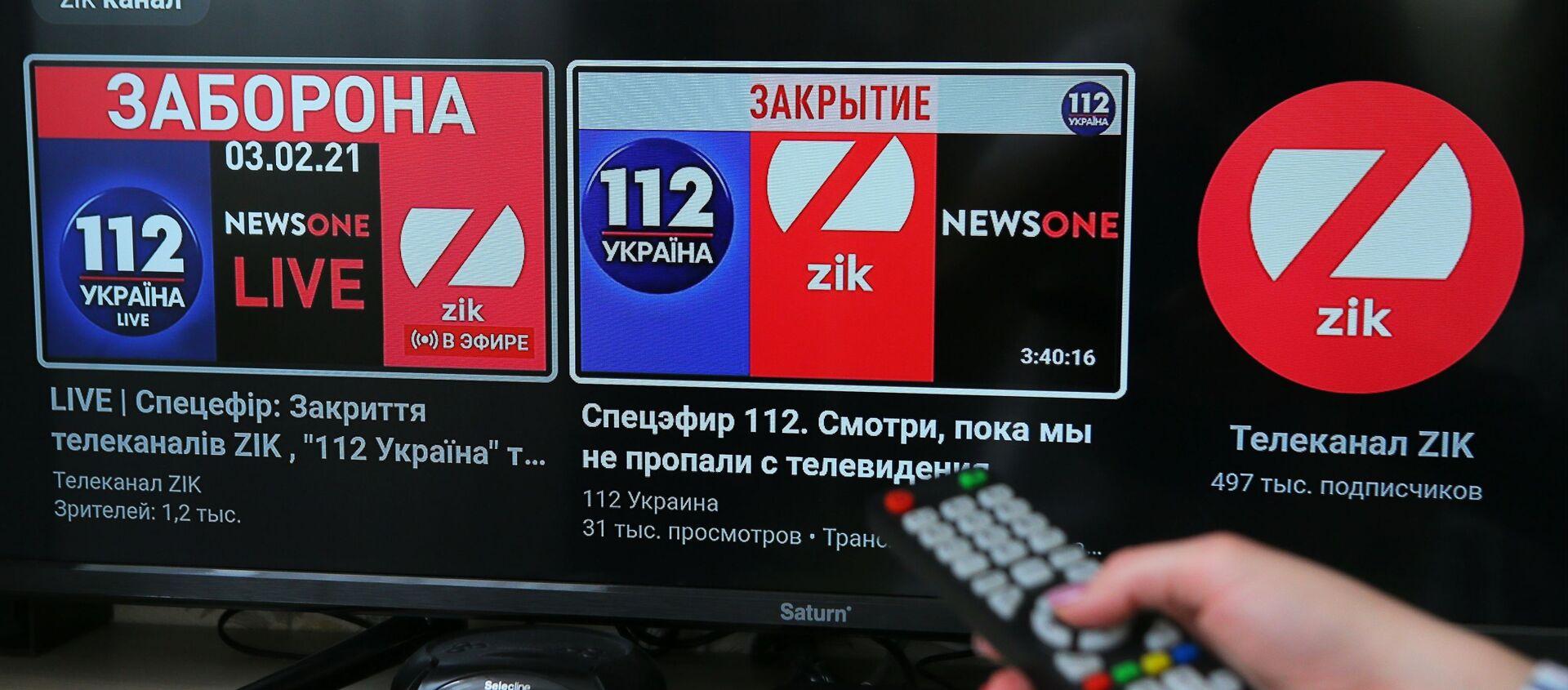 Экран телевизора с интернет-трансляцией телеканалов 112.Украина и ZIK  на платформе видеохостинга YouTube - Sputnik Узбекистан, 1920, 08.02.2021