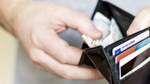 Человек держит кошелёк с деньгами - Sputnik Узбекистан