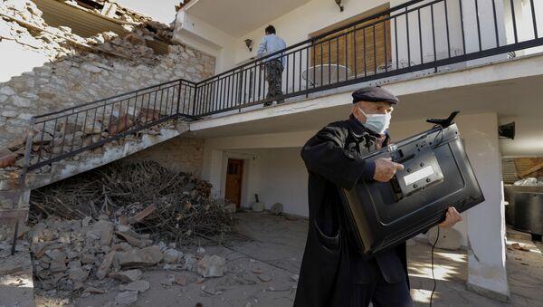 Мужчина с телевизором у поврежденного дома вследствие землетрясения в Греции  - Sputnik Узбекистан