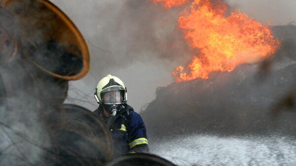 Пожарный тушит горящие шины - Sputnik Узбекистан