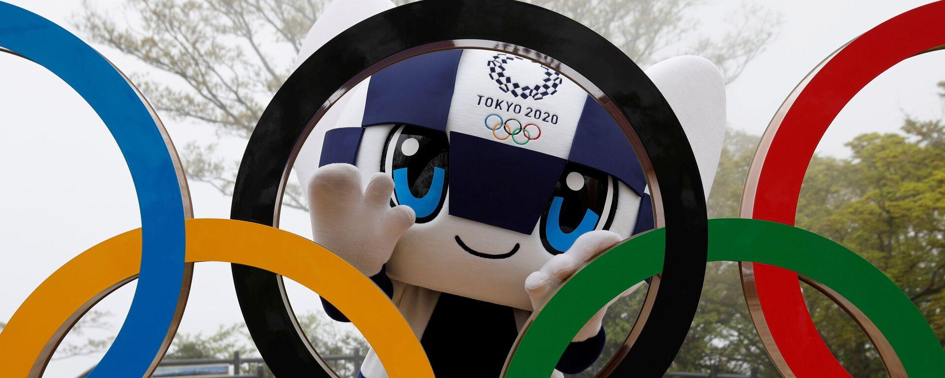 Талисман Летней Олимпиады в Токио Miraitowa позирует сзади Олимпийских колец после мероприятия по случаю 100 дней до Олийписких игр в Токио  - Sputnik Узбекистан, 1920, 28.04.2021