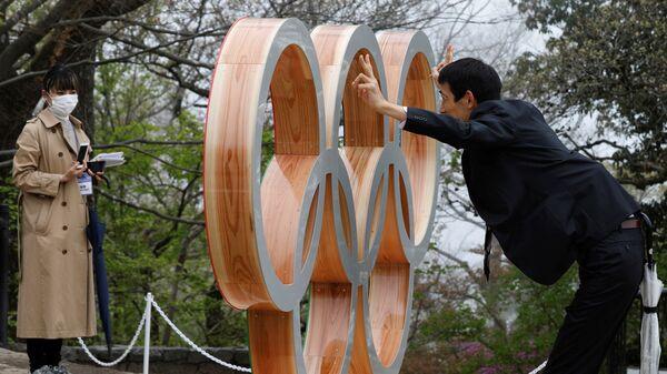 Мужчина фотографируется у Олимпийских колец после мероприятия по случаю 100 дней до Олийписких игр в Токио  - Sputnik Узбекистан