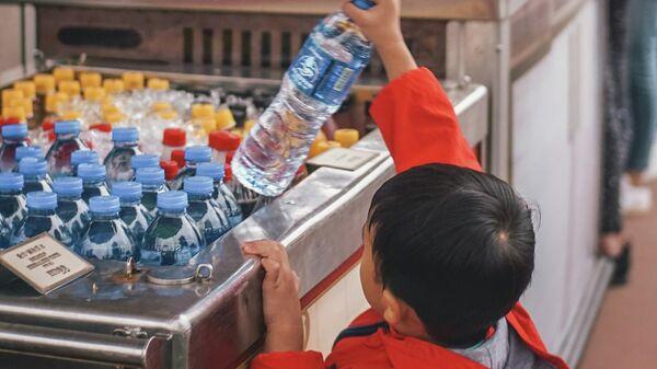 Ребенок достает бутылку с водой, иллюстративное фото - Sputnik Узбекистан