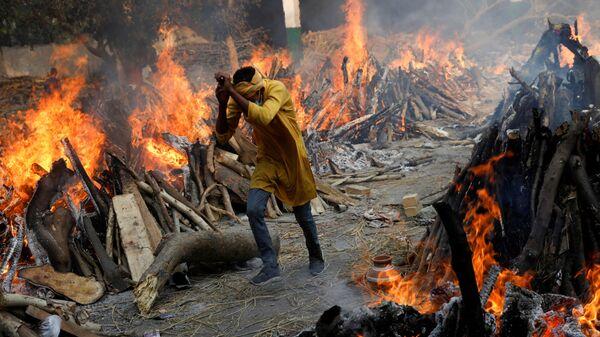 Погребальные костры во время массовой кремации в крематории в Нью-Дели, Индия - Sputnik Узбекистан