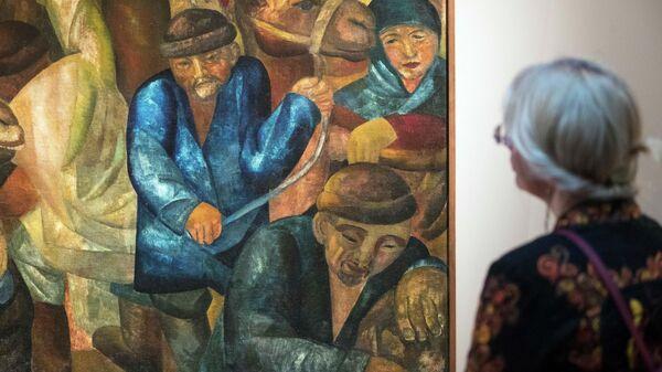 Посетитель смотрит на картину в Государственном художественном музее Каракалпакстана имени Савицкого в Узбекистане - Sputnik Узбекистан