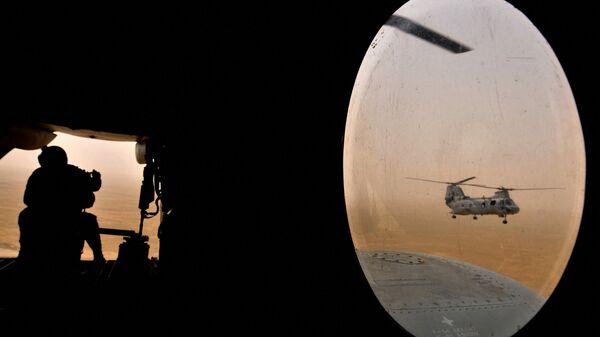 Amerikanskiy soldat (sleva) sidit v zadney chasti vertoleta morskoy pexotы Chinuk - Sputnik Oʻzbekiston