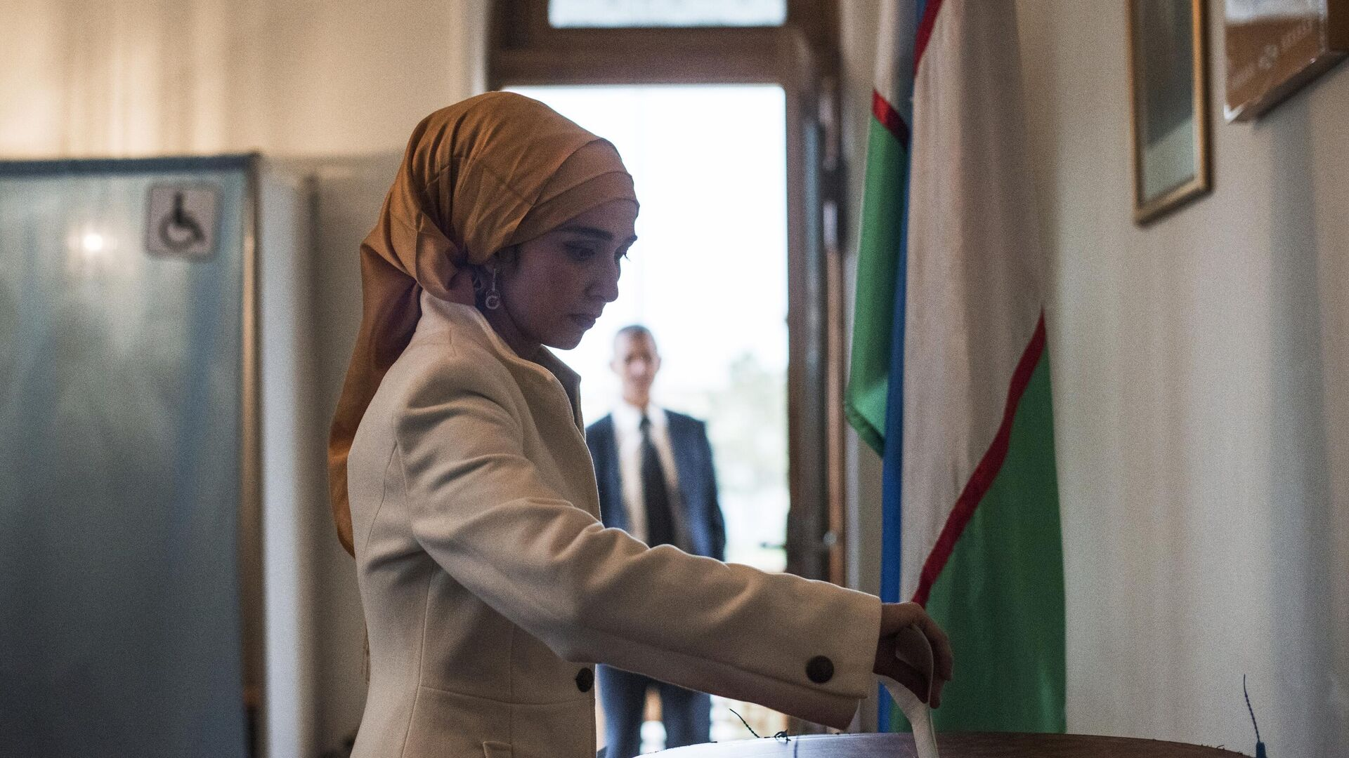 Женщина голосует на избирательном участке во время выборов президента Узбекистана - Sputnik Узбекистан, 1920, 30.09.2021