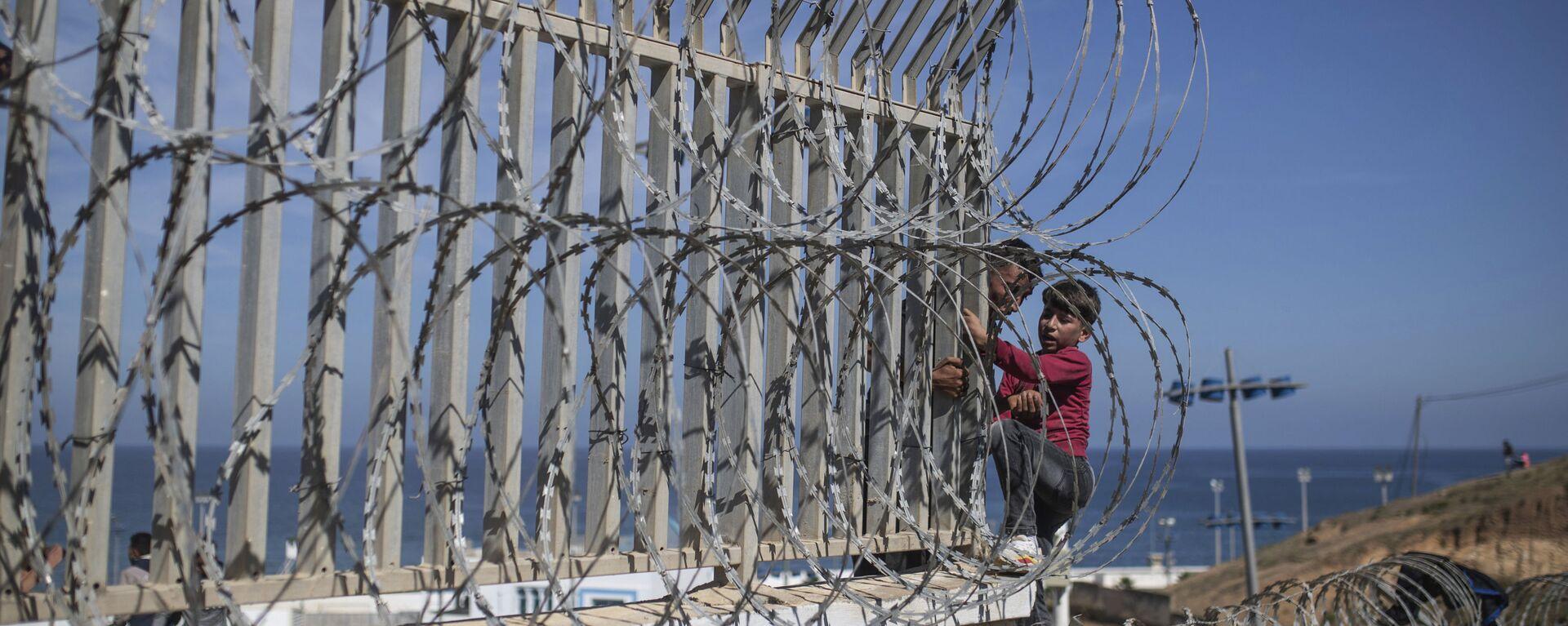 Мигранты перелезают через забор на границе Марокко и Испании, недалеко от испанского анклава Сеута - Sputnik Узбекистан, 1920, 24.07.2021
