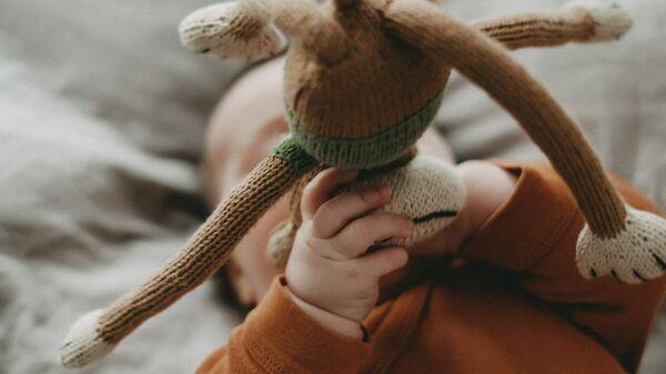 Младенец держит мягкую игрушку - Sputnik Узбекистан