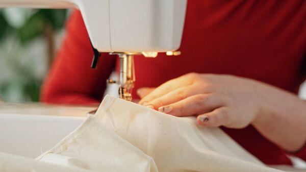 Женщина работает за швейной машинкой. Иллюстративное фото - Sputnik Узбекистан