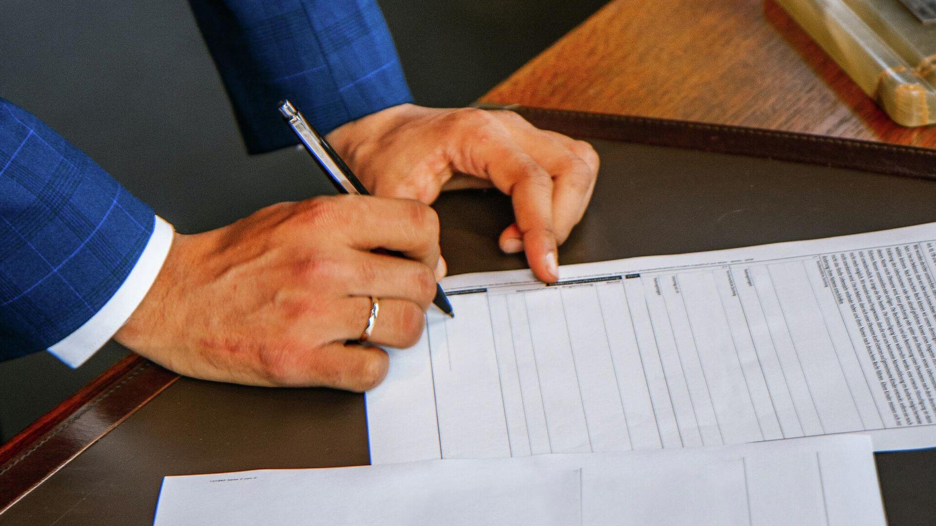 Мужчина подписывает документы. Иллюстративное фото - Sputnik Узбекистан, 1920, 26.09.2021