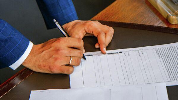 Мужчина подписывает документы. Иллюстративное фото - Sputnik Узбекистан