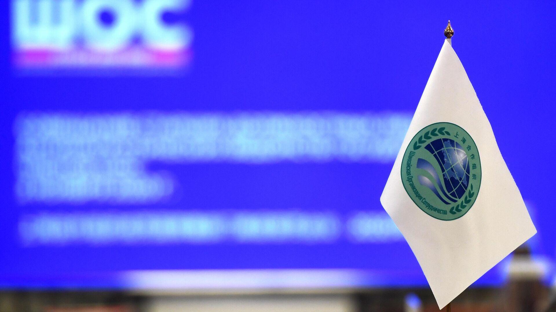 Флажок с логотипом Шанхайской организации сотрудничества (ШОС) - Sputnik Узбекистан, 1920, 16.09.2021