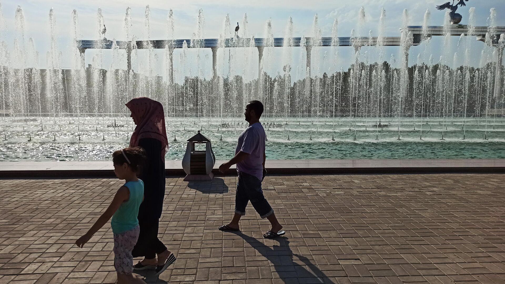 Семья освежается от прохлады фонтана - Sputnik Узбекистан, 1920, 13.10.2021