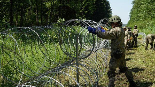 Солдаты литовской армии устанавливают забор из колючей проволоки на границе с Беларусью в городе Друскининкай - Sputnik Узбекистан